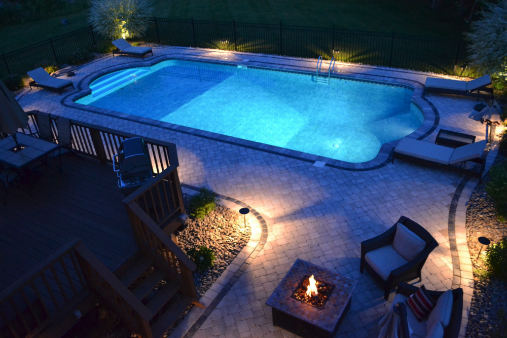 A pool patio built using Unilock pavers, including a fire feature by Landworx Landscaping in Goshen, NY