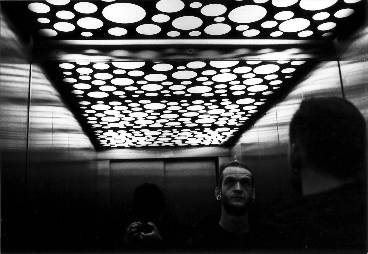 back from berlin (no.1)   i am back from berlin where i saw so many elevators that i started thinking about photos i've made inside elevators. there are a lot of them. why? i don't know why… maybe because of the light, the metal, the mirrors and the sterility in most of them. to me an elevator is something like the minimum unit of design and space inside a building (next to the toilets).   but ok. to stop writing such sentimental stories about every pic, or just because i don't remember where this was shot (which means if i could i still would write my story) here you get something without permanently praising the past. so what you can read now is not the story about this photo, it is just the occasion for posting it. does this make a difference to you? more than likely not.   you see my very good and also photography loving friend flo in a super futuresque high end design elevator, whose roof is supposed to imitate london by night. next to him is me holding my camera softly like the third  gin tonic  at 3 o'clock on monthly  space disco .    an awsome idea: who's able to say me where this elevator is, gets a limited aortalovesyou button from me. sounds like a crazy competition, doesn't it?
