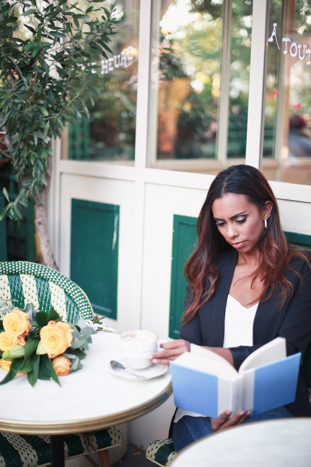 Vacation photo shoot in Paris with Flytographer. Woman sitting at cafe reading book in Paris