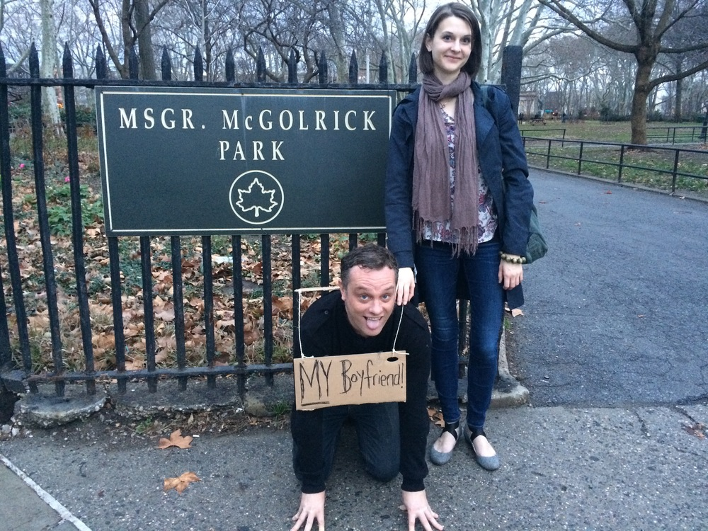 MY MY: My Selfie with My Boyfriend    2016    Video of Performance McGolrick Park, Brooklyn. Xmas Eve, 2015. 2nd Performer/Camera: Karolina May. 3rd Performer: Tony   I behave as a dog to a female owner, going to the park, chasing balls, with a 'MY Boyfriend' sign hung round my neck.  'My' neck. 'My' dog'. 'My' ball. 'My' boyfriend. I found a guy at a film festival. I found a dog on a doorstep. Do I then go on to possess them equally? Are they both, as the word suggests, mine? And why can we only have the singular 'my boyfriend', yet the plural, 'my friends'? Who made these rules? Why must we have dominion over our lovers, why must we own them, make rules for what they can do and who they can see, grant and withhold our love? All these questions can be seen in the metaphor of dog and owner, as examined in this performance.  At the same time, this performance is an embodiment of the real life circumstances of the performers. Two weeks prior to this, the woman performing, Karolina May, told me, the man performing, we were through. Since we'd met two and a half years prior, where she'd been nothing but loving, I had been voicing the arguments above, telling her I didn't want a relationship, I didn't believe in monogamous love, that if she needed that stupid crap she could go get herself someone normal. Well, bless her, she finally woke up and did. And it was then, of course, that I realized I'd been full of shit the whole time, that I'd been hiding behind my intellectual arguments to protect myself, and here, before me, was the love of my life.  Too late now, stupid doggy.  In fact one of the most painful sentences I've ever had said to me was the seemingly benign 'Don't put that in the video' she says at the end. I, on my knees, literally, begging for her back, like a dog, trying to steal a kiss, and she not wanting anyone who saw this to think — for even a second — we were still together.