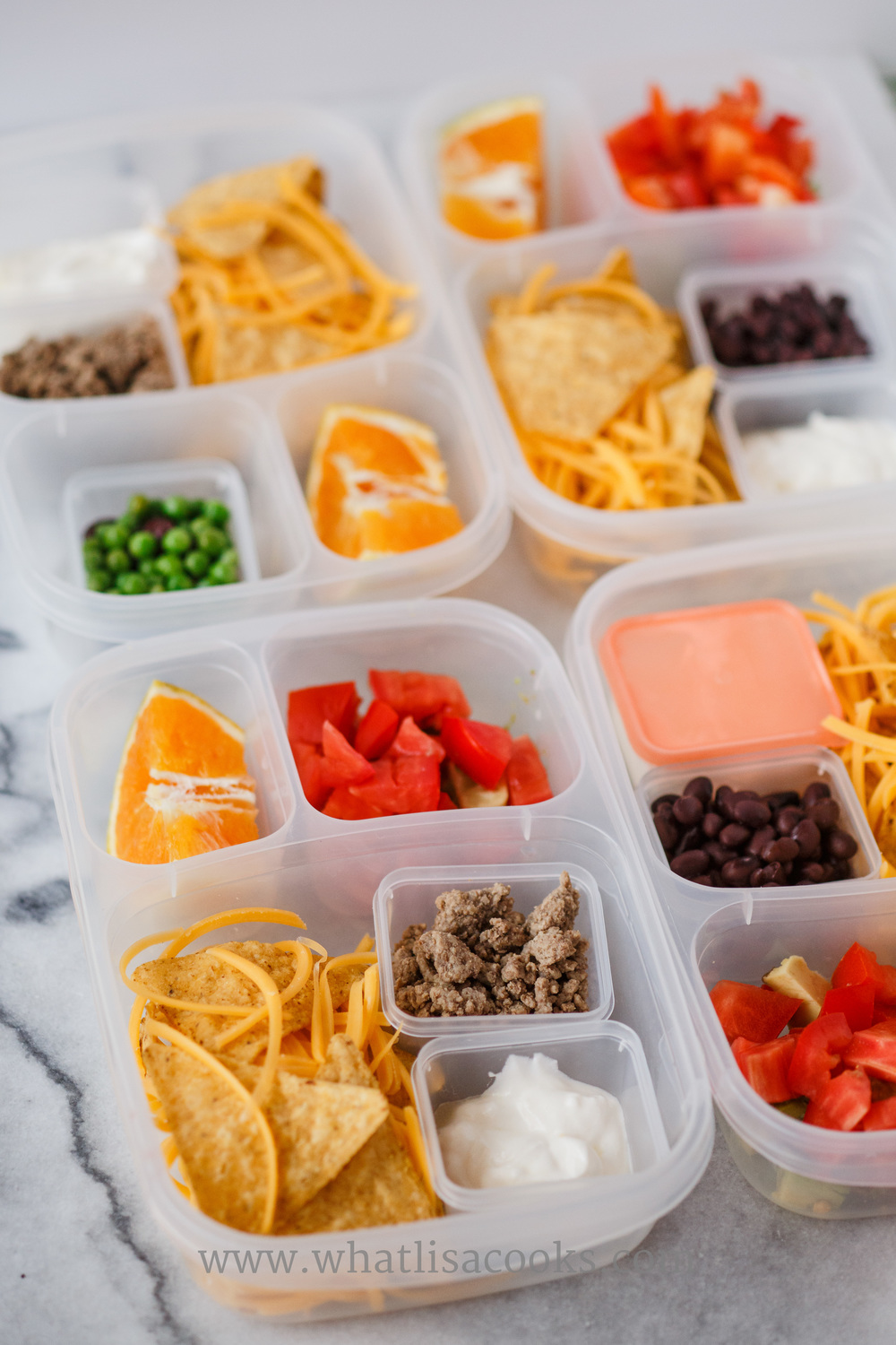 Nacho kits: tortilla chips, shredded cheese, meat or beans, sour cream.  Three have tomatoes and avocados with lime juice, one has black beans and peas.
