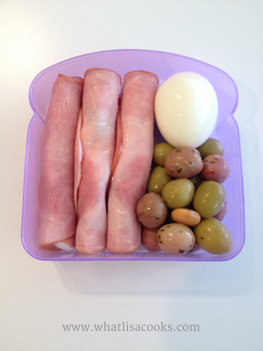 Little sandwich boxes are the perfect size for a small meal.  This was a protein packed, low carb, power lunch.  Slices of ham spread with cheese and rolled around a pickled asparagus, with boiled egg, marinated olives.