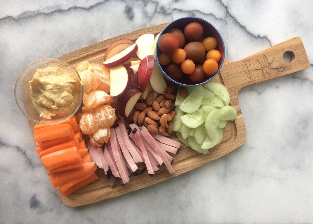 Carrots, hummus, oranges, ham, apples, almonds, cucumber, and tomatoes.