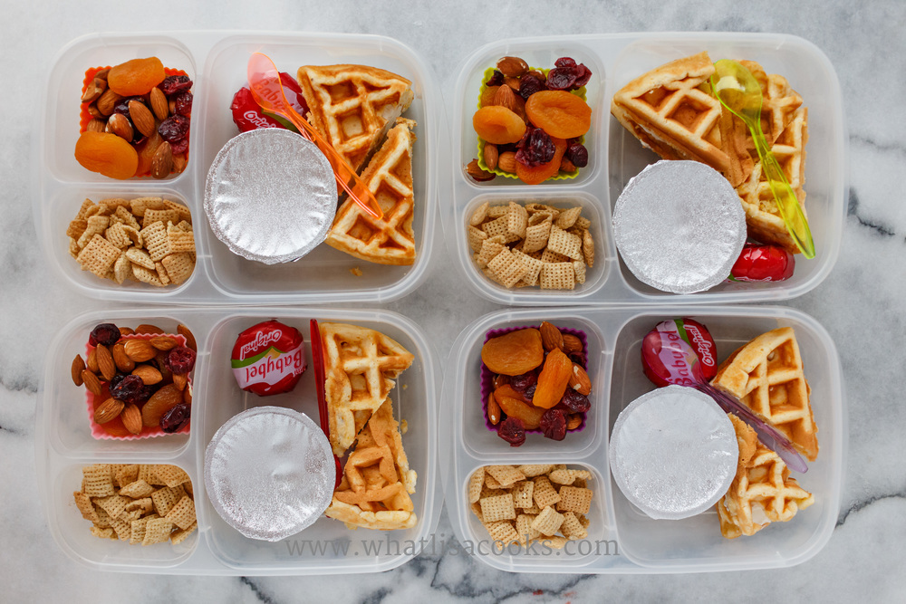 Waffle sandwiches - three have cream cheese and one has butter; with cheese, applesauce, chex, and a trail mix of almonds, raisins, cranberries, apricots.