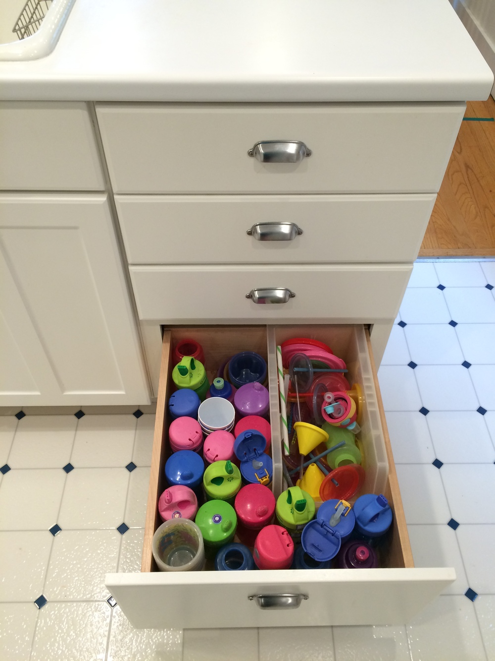 In the kitchen I keep all the kids cups and water bottles in a bottom drawer that they can reach. Up until very recently I also had plastic plates and bowls here, but we don't use them any more so they were cleaned out.  In the drawers above this I have dish towels, washcloths, and plastic bags & wraps.