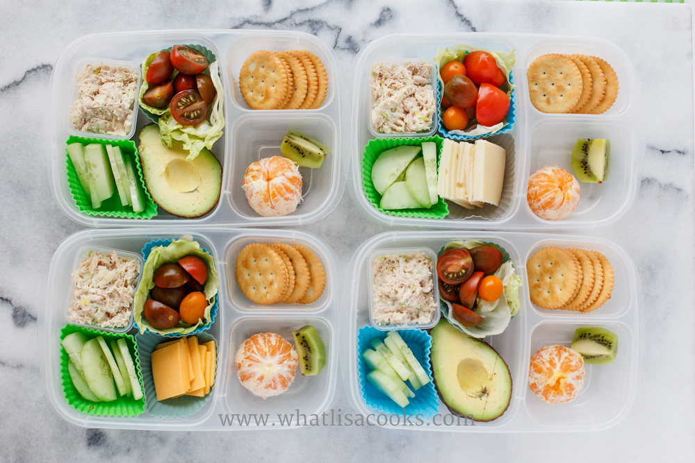 Chicken salad, cucumbers, tomatoes, orange and kiwi.  Two have avocado, two have cheese.  Serve with gluten free crackers.