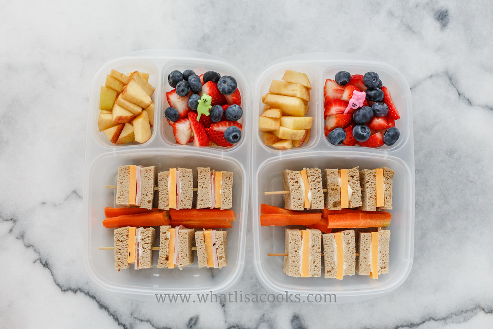 Mini sandwich skewers.  Grain free blender bread from Against All Grain, one has mayo, ham and cheese, the other has butter and cheese, with strawberries, blueberries, and apples on the side.
