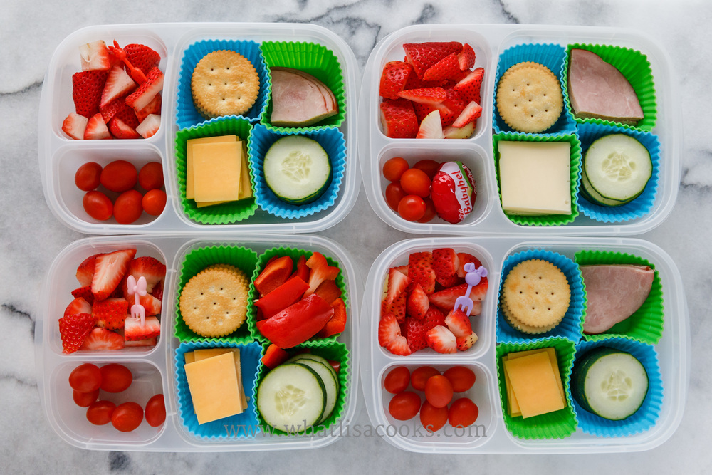 """""""Lunchable"""": crackers, ham, cheese, cucumbers, tomatoes, strawberries. The one without ham has sweet red peppers, and the one with the biggest appetite got an extra cheese. Packed in  Easy Lunchboxes , with  square silicone muffin cups. , and little  Minnie Mouse bento forks."""