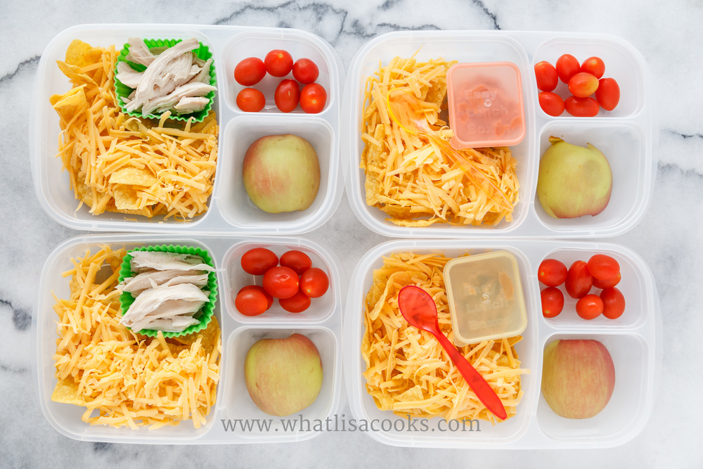 Tortilla chips, shredded cheddar cheese, apple, & tomatoes.  Two have refried beans and two have shredded chicken.  Packed in  Easy Lunchboxes , with  mini dipper containers  for the ketchup,  silicon muffin cups  for the chicken, and  disposable plastic baby spoons .
