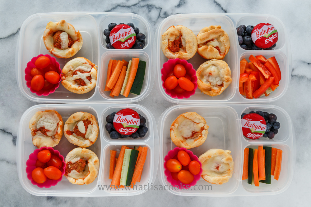 Pizza muffins and meatball muffins,  with tomatoes, carrots, cucumbers, blueberries, and cheese. Packed in  Easy Lunchboxes , with pink silicone muffin cups from Ikea.