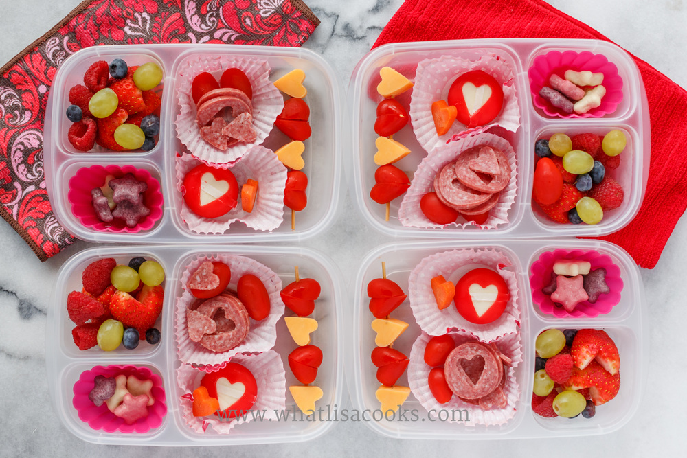 Salami, cheese, tomatoes, grapes, strawberries, and yogurt covered cookies.