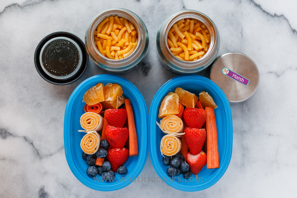 Leftovers for two: macaroni and cheese, tortilla and cheese rolls, with strawberries, blueberries, oranges, and carrots.
