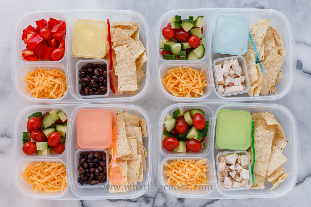 Deconstructed nachos: corn chips, cheese, sour cream, two have chicken and two have beans. On the side: tomatoes, sweet peppers, zucchini.Packed in Easy Lunchboxes .