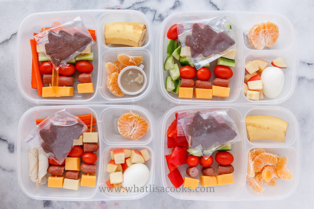Mini skewers with cheese, hot dogs, tomatoes, cucumbers. More veggies on the side, fruit, boiled eggs, and a Christmas cookie for a treat.