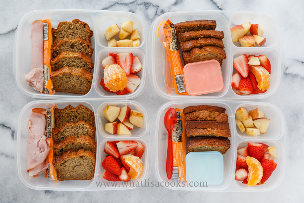 Homemade whole wheat banana bread, cheese, apple, strawberries.  Two have ham and two have yogurt. Packed in  Easy Lunchboxes .