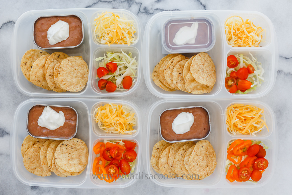 Refried beans, sour cream, corn tortilla chips, cheese, cabbage and tomatoes. Packed in  EasyLunchboxes .