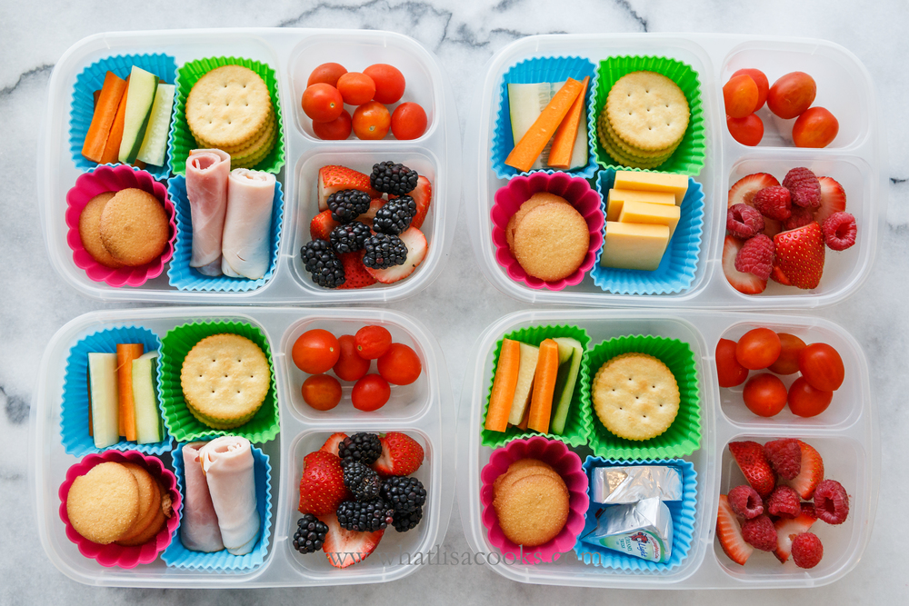 Lunchable with crackers, cheese, veggies, tomatoes, berries.