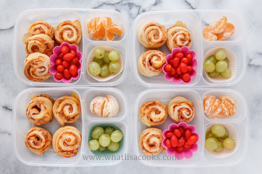 Pizza rolls, tomatoes, grapes and oranges.