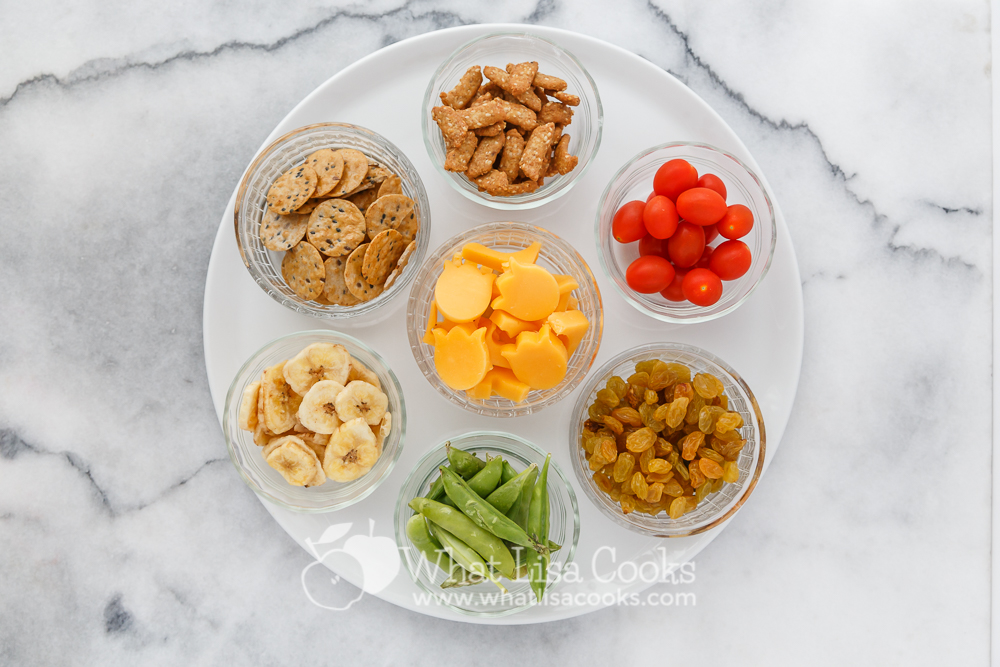 Little glass bowls make a pretty serving. This plate has rice crackers, sesame crackers, tomatoes, raisins, sugar snap peas, cheese, and dried bananas.