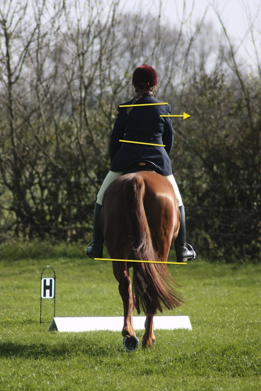 This image shows a rider sitting asymmetrically in the saddle. You can easily see that her hips and shoulders aren't level, her stirrup heights are uneven and that her weight has shifted over to the right. Image: © Joingate |   dreamstime.com