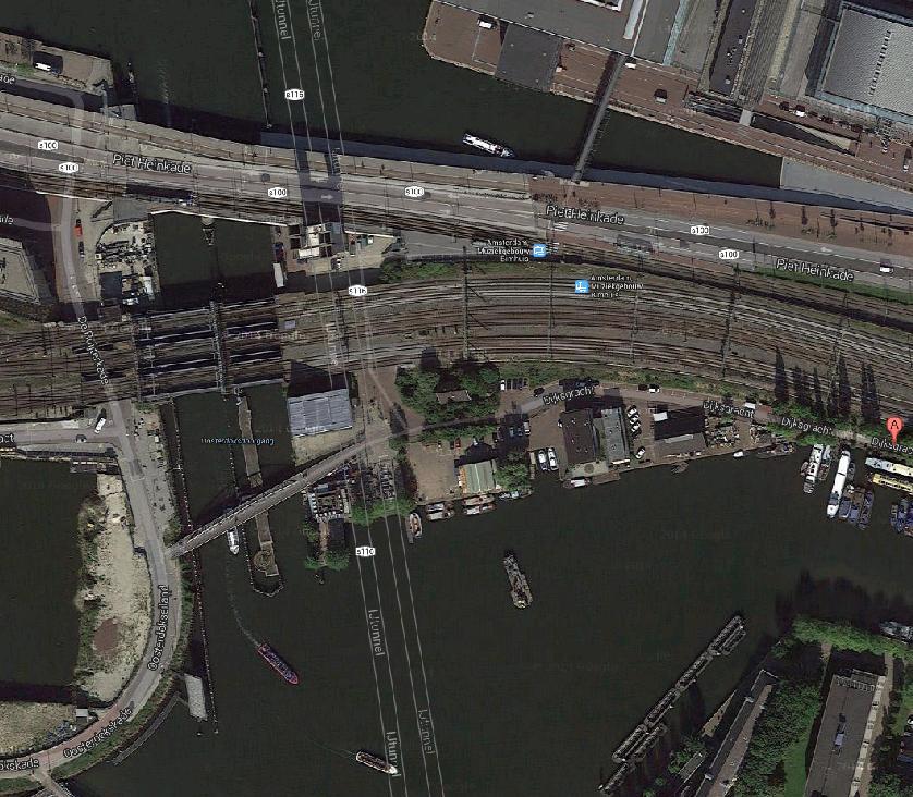 Kop Dijksgracht. De klimmuur aan de Oosterdoksdoorgang blijft gehandhaafd. Aan de Dijksgracht komen/blijven van links naar rechts: Hannekes Boom, toekomstige ligplaats horecaschip Barco, toekomstige Shaffy's tuin (zelfbeheer), vm. DIVV-werf wordt Mediamatic broedplaats, locatie tijdelijke brug naar Marineterrein,