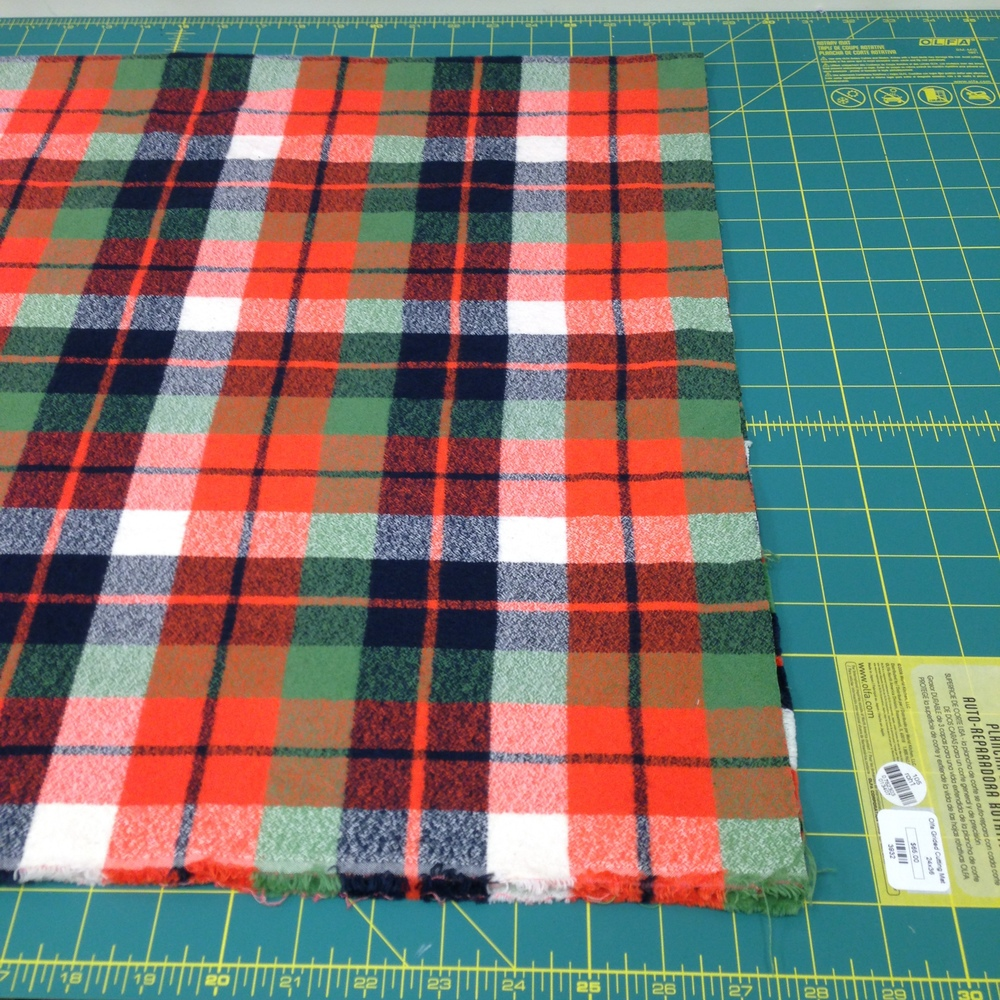 Using a gridded cutting mat or table is a great way to check if your fabric is aligned. Once folded, it should match up with the lines on the table, just like in the pink gingham swatch shown in the beginning.