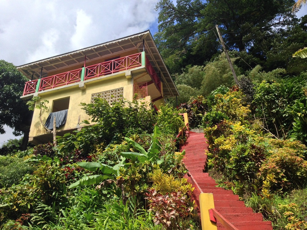 A mountain home near a waterfall in Grenada, painted in the national colors.