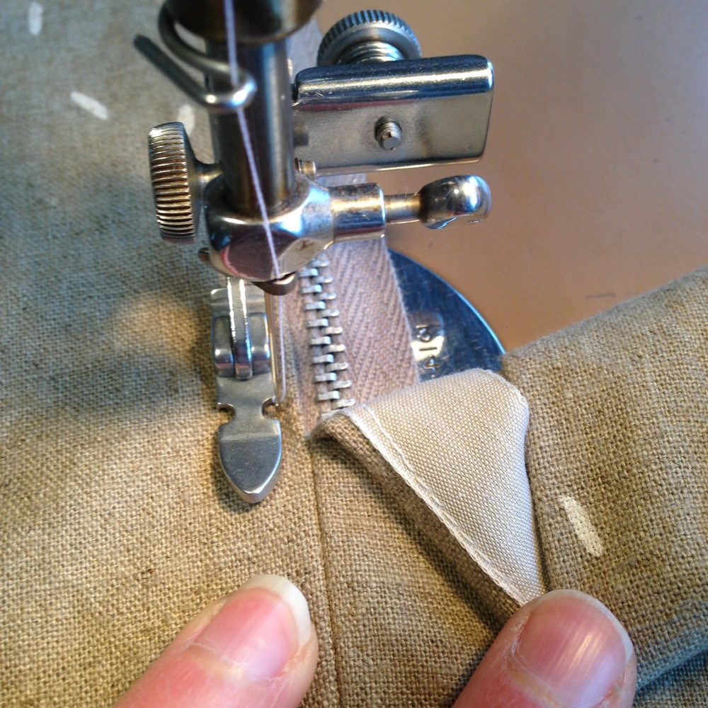 In this picture, I've attached a ribbon to my zipper seam allowance to give me both a clean finish inside and to add extra width to my seam allowance to be sure that I catch it while sewing the lapped part of the zipper. You can also cut your seam allowance at the zipper a bit wider, a technique included in the A-Frame pattern.