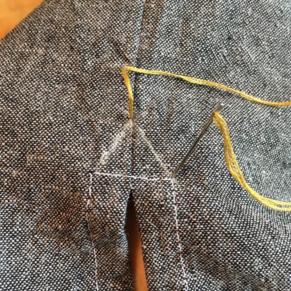 First, draw in your little triangle as a guideline. With a strand of embroidery floss, pearl cotton or buttonhole thread, come up through the top of the triangle, then down through one bottom corner.