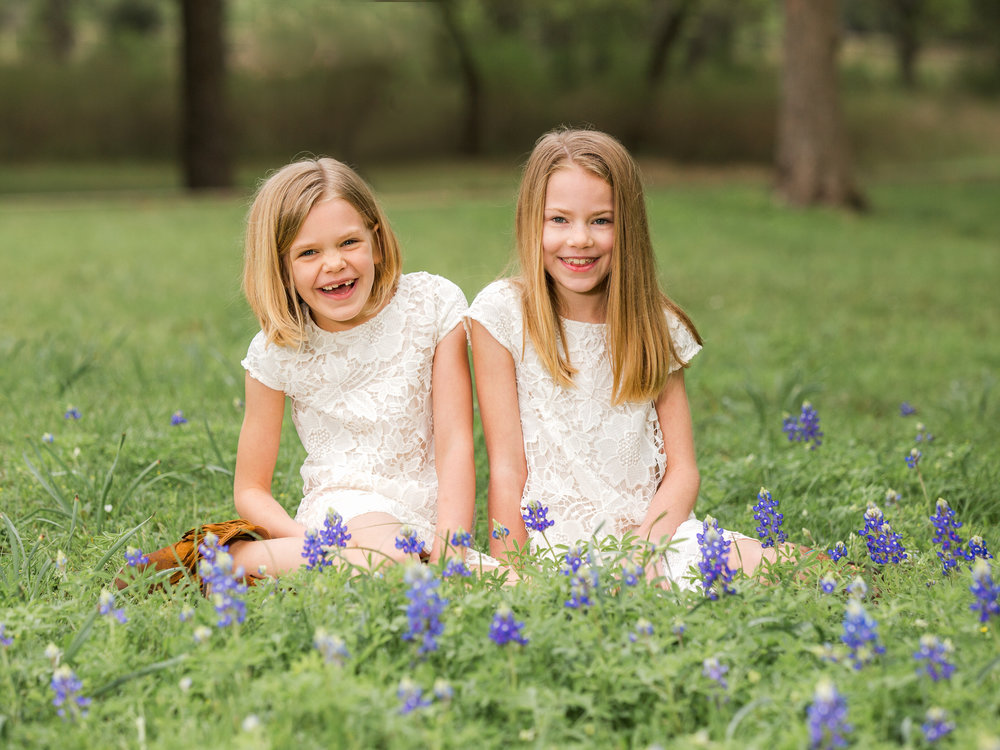 Young sisters in an early springtime bluebonnet field. | Texas Hill Country Portrait Photographer