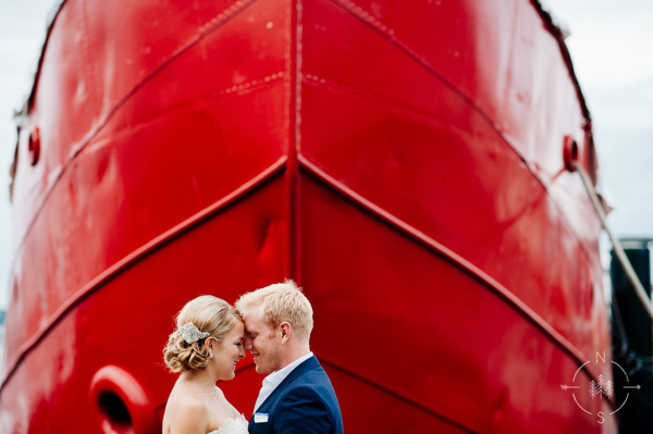 bride and groom nuzzle in front of ship bow