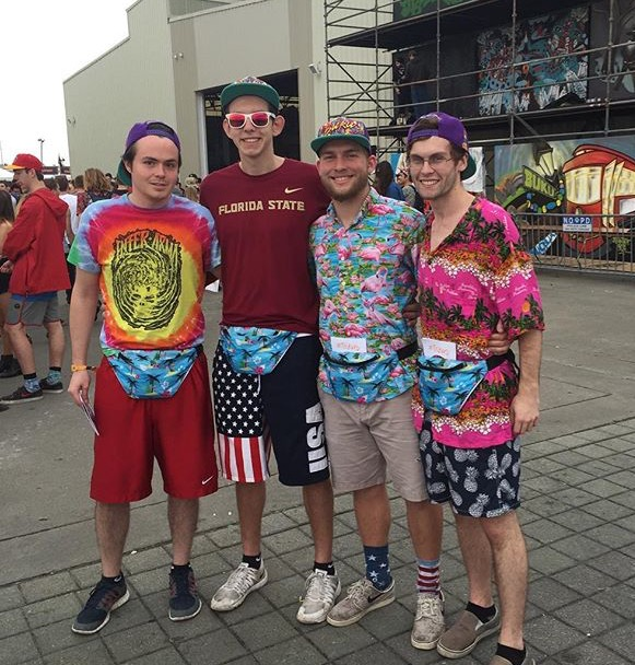College guys show off their tropical shirts and matching fanny packs while at the festival.