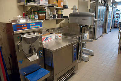 Staff prepare pizza dough in the mixer and gelato in the machine that both heats and freezes.