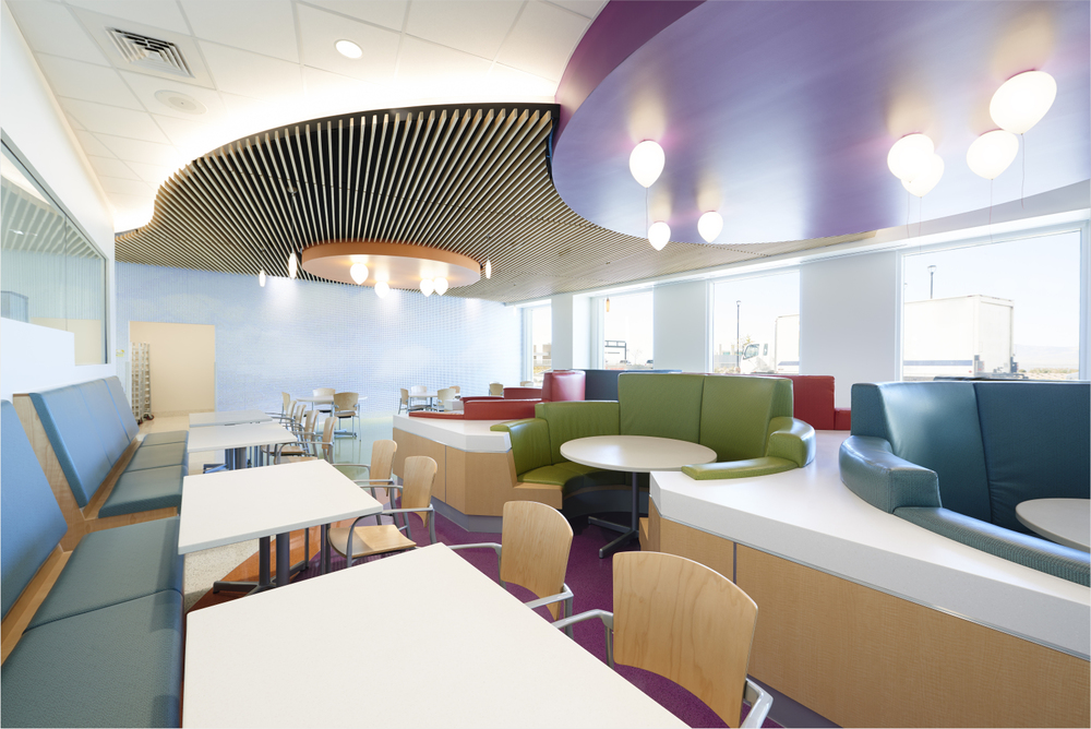 Booths stand out with their colorful palette of orange, purple and lime green in the front of the dining area. The booths are very useful for meetings, because they have high seat backs, which create a sound barrier.