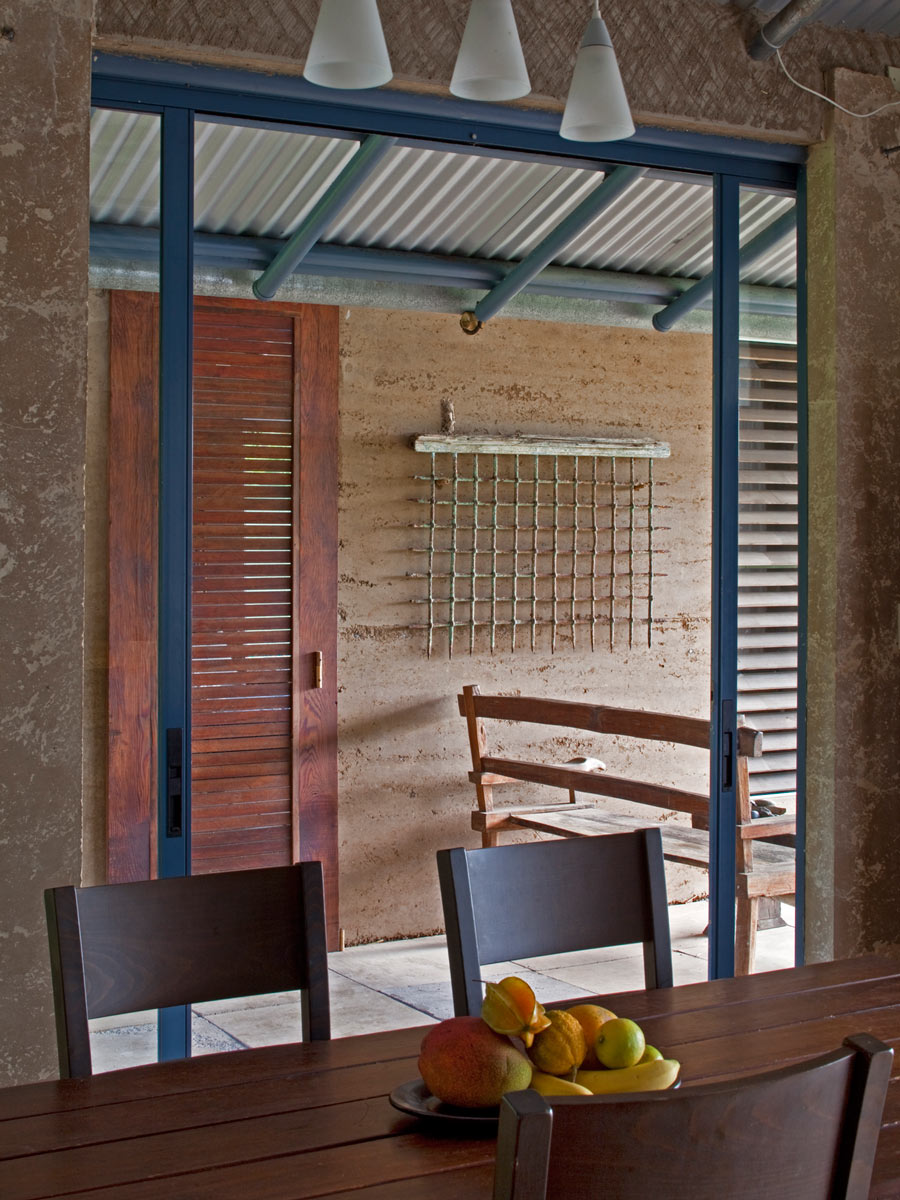 View through the sliding dining room wall glass panels into the breezeway. Tradewinds pick up speed as the funnel through the breezeway, pulling heat from the living spaces.   Image © Art Gray