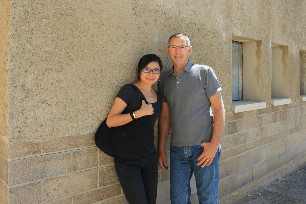 Dr. Rongrong Hu and David Easton at the Watershed Materials headquarters, standing in front of a building made with rammed earth Watershed Block below rammed earth PISE.