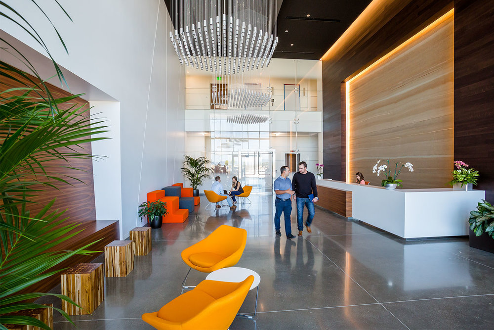 The new rammed earth, slimmed down and ready for the show, complements the palette of crisp, modern finishes in the lobby of the six-story Stadium TechCenter in Santa Clara, California. Interior design by SmithGroupJJR.