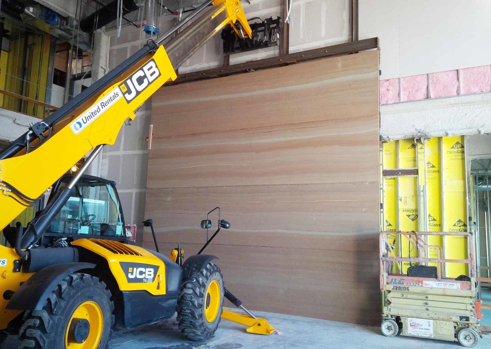 For the installation of the four big Stadium TechCenter panels, we used a long reach forklift to set the panels rather than a crane because the roof was already on the building. The forklift picked each of the twenty-two foot long by five foot high panels off the truck, backed directly into the lobby with only inches to clear the door frames, executed a ninety-degree turn and placed the panels one on top of another against four steel posts where they were welded in place.