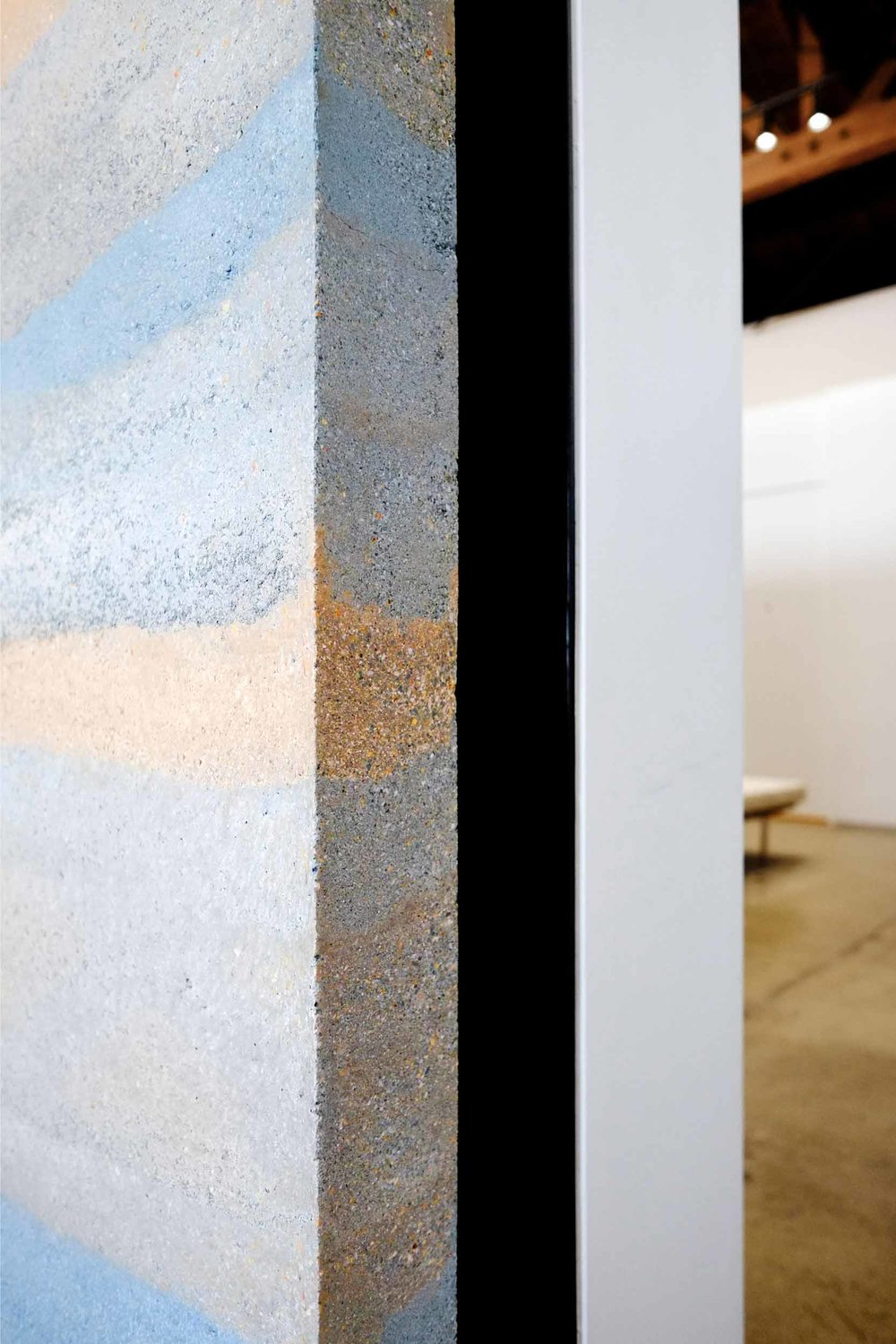 "Pre-cast thin interior rammed earth panel at the Reformation store in Los Angeles. After curing in the shop for a month, each of the panels was cut in half to facilitate transport, then re-assembled in the store and mounted onto a square tube steel frame bolted to footings beneath the original concrete slab floor. The ""end grain"" of the cut panels reveals the small stones and gravel that are a component of the formulations that give each layer its strength and color. Image © Jesse Gillan"