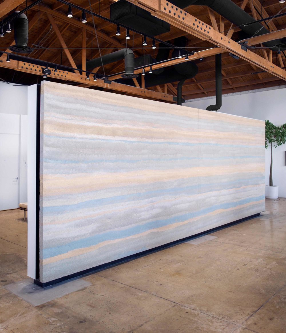 The interior of newest Reformation store, located a few blocks east of Beverly Hills, features a 200 square foot free-standing mural of stratified rammed earth floating above a polished reclaimed concrete slab - nearly naked.  These thin slabs of rammed earth are like nothing else. Everywhere in the world, rammed earth walls are thick, massively heavy, and constructed right at their final resting place. Making rammed earth thin enough to put on a truck, carry into a building, and hang on a wall is a paradigm shift for the earth building industry.  Image © Jesse Gillan