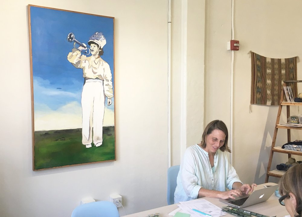 Sara Heckman, owner, sitting beside one of her paintings. The work was inspired by a vintage photograph of a girl in her band uniform on the front lawn of her house.