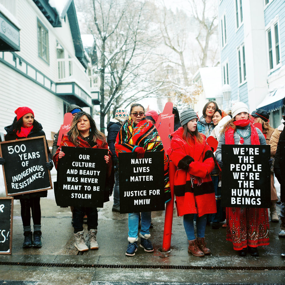 Photo By: Jonathan Canlas  PANDOS's Missing and Murdered Indigenous Women Committee gathered on Main Street in Park City, Sunday January 20th around 12pm during the Sundance Film Festival, to raise awareness for this brand new campaign.  We handed out Red Doll pins and postcards to inform the public about this important issue.  The Committee seeks to monitor, research, and organize on the issue of Missing and Murdered Indigenous women in the Intermountain West and South West regions. We seek to build relationships with tribal governments, municipal governments, and state and federal officials to better understand the barriers that prevent us from being able to address the atrocities perpetrated against our indigenous women. We seek to address the conditions that contribute to violence against women, and the deafening silence that follows. We seek to be the voice for people who can no longer speak for themselves.