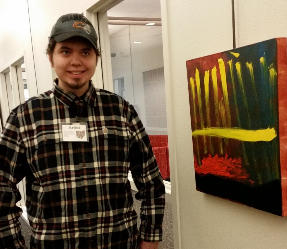 "Jesse proudly poses beside his painting ""Jesse's Comet"" (first place winner in the Professional Artist Category)"