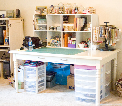 Storage drawer units in this craft station, along with open shelving units sitting on top the desk work.