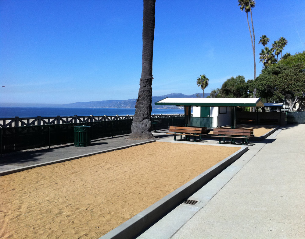 The petanque courts are located in the 1400 block of Palisades Park, just south of the Camera Obscura building at 1450 Ocean Avenue.