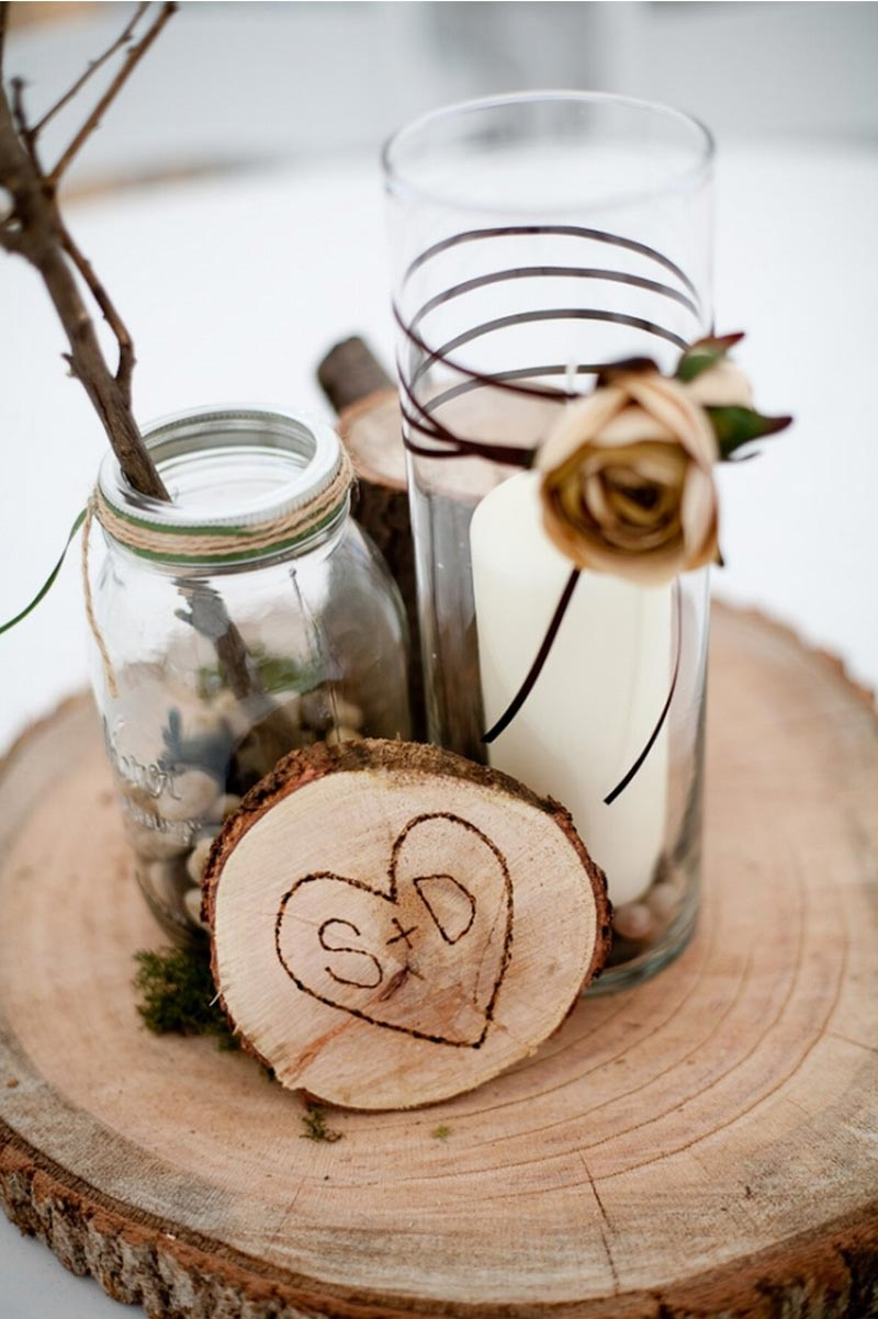 natural-winter-wedding-centerpieces-with-white-candles-and-flower-inside-glass-above-wooden-board.jpg