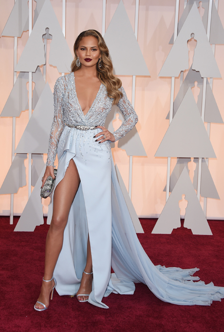 Chrissy Teigen in Zuhair Murad:  Wow! Glittering long-sleeved elegance. The gowns plunging neckline is sexy and sensual. The soft fabric is filled with crystal-embellishments and perfect with strappy stilettos. This would be the perfect reception gown but may be a little risque for the ceremony.