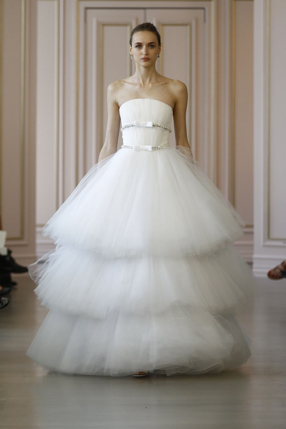 Stasha White tiered tulle ball gown wedding dress, jewel encrusted grosgrain ribbon detail. Silver and crystal earring, white ribbon embroidered sandal.