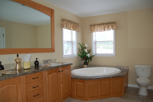 MASTER BATH SHOWING DOUBLE VANITY, PLATFORM TUB, AND FRAMED MIRROR (HONEY STAINED MAPLE CABINETRY)