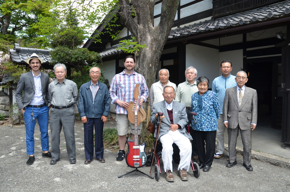 Frank Meyers' meeting in 2013 with some of the current and retired Fujigen employees. He presented his EJ2 back to them and their museum. In return, they presented him with the first prototype of the EJ style body. Fujigen's first electric guitars were the EJ series.   They are standing in front of Yoichuro Yokouchi's house in Matsumoto,  who started the company in 1960. (Seated in front is Yoichuro Yokouchi.)